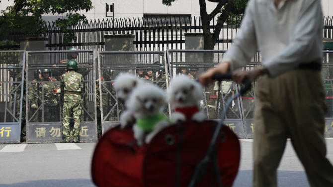 A man strolls with dogs on a baby cart as paramilitary police officers arrange the steel fence in front of the Japanese Consulate General in Shanghai, China, Wednesday Sept. 19, 2012. China was returning to normalcy Wednesday after angry protests over Japan's wartime occupation and Tokyo's recent purchase of islands also claimed by Beijing. (AP Photo/Eugene Hoshiko)