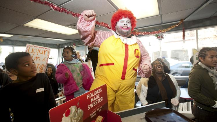 A demonstrator dressed as Ronald McDonald, who declined to give his name, protests inside a McDonald's restaurant demanding higher wages for employees in Oakland