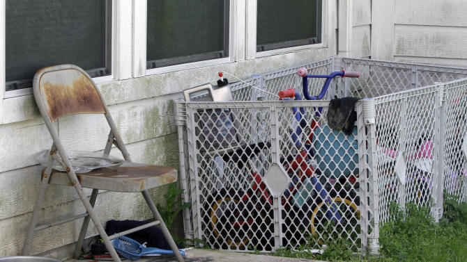 A rusty chair and some toys sit outside a Dayton, Texas, house Tuesday, Feb. 21, 2012, where 11 children, some of them reportedly found in restraints,  where removed by children's protective services last month. Texas authorities said Tuesday, Feb. 21, 2012, that they removed 11 children last month from the home where a registered sex offender lives after they found eight confined in a small, dark bedroom with restraints tying some to their beds. One month after a raid on the house, authorities are still trying to determine how the children are related and why they were there, Child Protective Services spokeswoman Gwen Carter said.  Along with the children, 10 adults were living in the one-story, 1,700-square-foot home.  (AP Photo/Pat Sullivan)