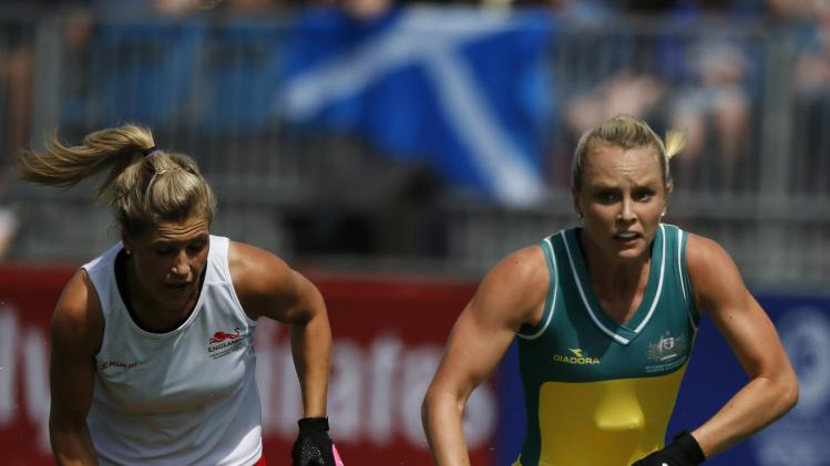 England's Georgie Twigg and Australia's Jane Claxton compete for the ball during their hockey match at the 2014 Commonwealth Games in Glasgow, Scotland