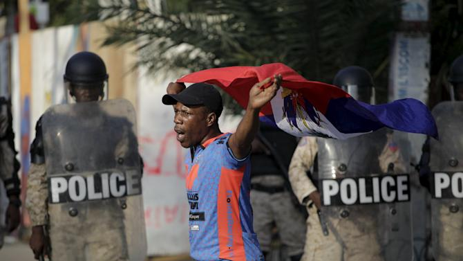A protester holds a flag in front of National Police officers during a demonstration called up by opposition groups in Port-au-Prince, Haiti