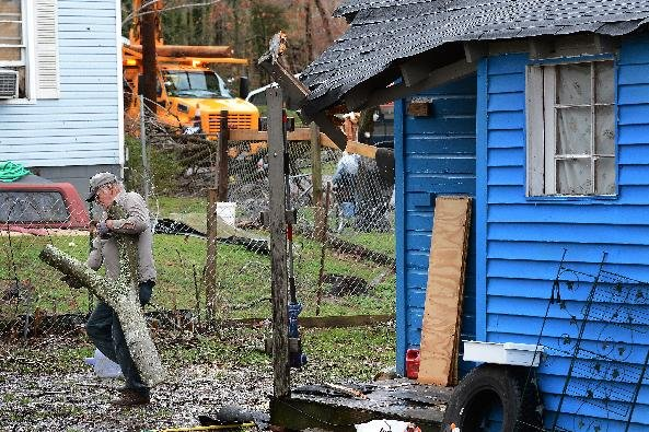 Thomas Ivey carries section of a tree he cut up after it was blown over by tornado that hit the corner of his friend's house     Wednesday, Jan. 30, 2013, in Ashland City, Tenn. Around 25 homes in Ash