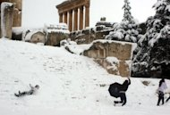 The Roman temple of Jupiter is seen in the background as Lebanese youths play in the snow on January 9, 2013. The worst storms in a decade left swathes of Israel and Jordan under a blanket of snow and parts of Lebanon blacked out, bringing misery to a region accustomed to temperate climates.