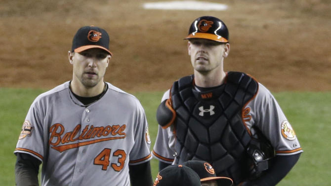 Baltimore Orioles' Mark Reynolds and Manny Machado embrace as teammates Jim Johnson, left, and Matt Wieters approach after the Orioles defeated the New York Yankees 2-1 in Game 4 of the American League division baseball series Thursday, Oct. 11, 2012, in New York. (AP Photo/Peter Morgan)