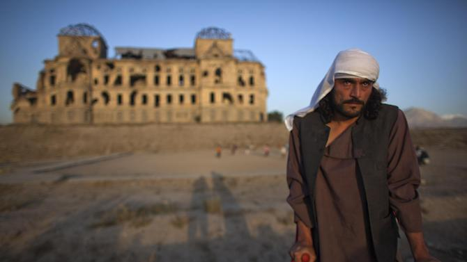 In this Thursday, Oct. 4, 2012 photo, Wahidullah, 32, whose spine was pierced by a bullet during the civil war that left him crippled, poses for a photograph in front of Darul Aman Palace which was damaged during the civil war in Kabul, Afghanistan. Wahidullah was a teenager when he fought in west Kabul during the civil war. (AP Photo/Dusan Vranic)