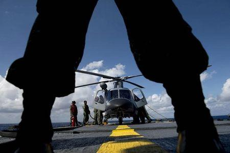 A Philippine Navy personnel stands in front of an Agusta Westland AW109 helicopter before it takes off during CARAT 2014, aboard Philippine Navy vessel BRP Ramon Alcaraz in the South China Sea near waters claimed by China