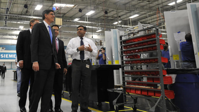 Treasury Secretary Jacob Lew, center, tours the Siemens manufacturing plant with manager Shujath Ali, right, where electrical drive components for heavy machinery are assembled in Alpharetta, Ga., Thursday, March 14, 2013. The facility produces large traction drive trains for customers including AMTRAK, Caterpillar and the new Atlanta Streetcar initiative. (AP Photo/David Tulis)