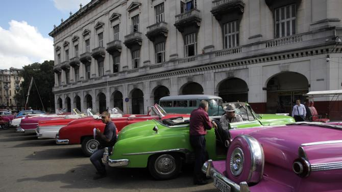 Drivers stand near their vintage cars waiting for clients in Havana