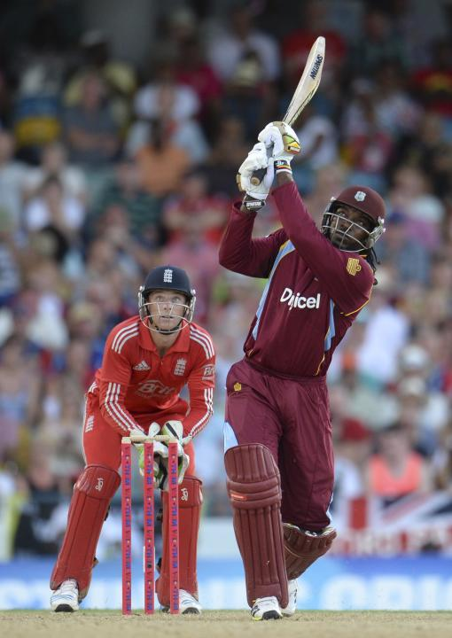 West Indies' Gayle hits a six watched by England's Buttler during the second T20 international cricket match at Kensington Oval in Bridgetown, Barbados