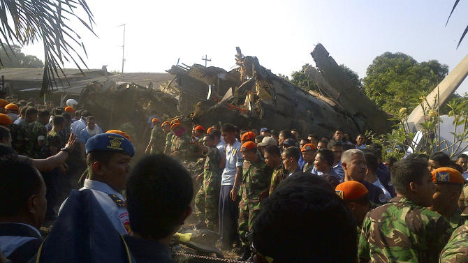 Military personnel inspect the site where an Indonesian air force plane crashed, in Jakarta, Indonesia, Thursday, June 21, 2012. The Fokker F-27 turboprop plane slammed into homes and ignited a fireball in the crowded capital while trying to land Thursday, killing at least nine people, a military official said.  (AP Photo)