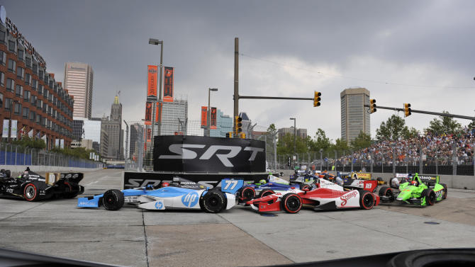 From left to right, Dario Franchitti, of Scotland; Simon Pagenaud, of France; Justin Wilson, of England, and James Hinchcliffe, of Canada, negotiate a hairpin turn during the IZOD IndyCar auto race for the Grand Prix of Baltimore, Sunday, Sept. 2, 2012, in Baltimore. (AP Photo/Gail Burton)