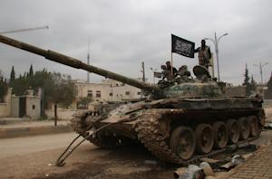 Fighters from a coalition of Islamist forces stand…