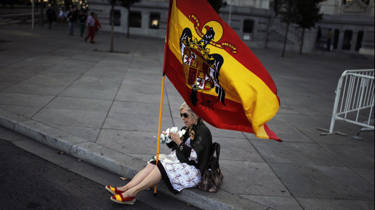 A woman holds a pre-constitutional flag as she eats a cake while sitting on the street during a military parade on the holiday known as Dia de la Hispanidad, Spain's National Day in Madrid, Saturday, Oct. 12, 2013. (AP Photo/Andres Kudacki)
