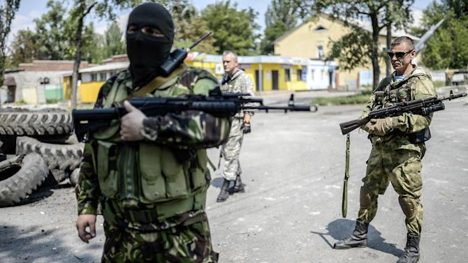 Pro-Russia separatists stand at their checkpoint near the front line in the northern outskirts of city of Donetsk, on July 22, 2014
