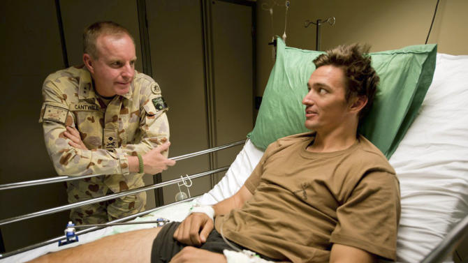 "In this undated photo provided by Maj. Gen. John Cantwell, left, the general talks with an unidentified injured man at an undisclosed location in Afghanistan. Cantwell could see the ridges and calluses of the skin, and the pile of desert sand that had swallowed the rest of the Iraqi soldier. The troops Cantwell was fighting alongside in the Gulf War had used bulldozing tanks to bury the man alive. This hand - so jarringly human amid the cold mechanics of bombs and anonymous enemies - was about to wedge itself, the Australian man would write decades later, ""like a splinter under the skin of my soul."" It would lead, along with other battlefield horrors, to the splintering of his mind and to a locked psychiatric ward. (AP Photo/Maj. Gen. John Cantwell, Sergeant Neil Ruskin) EDITORIAL USE ONLY"