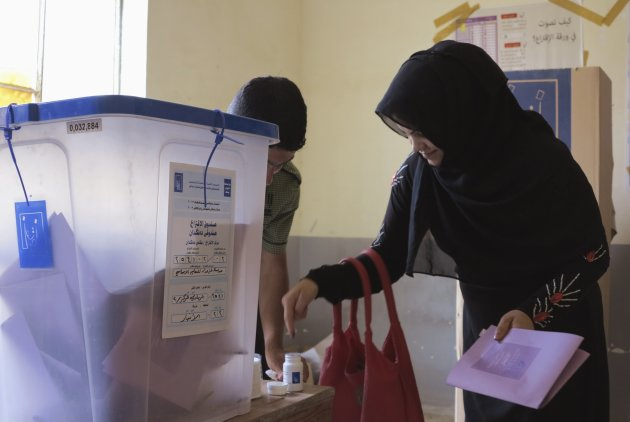 A woman dips her finger in ink while voting during the Iraq's provincial elections at a polling station in Ramadi