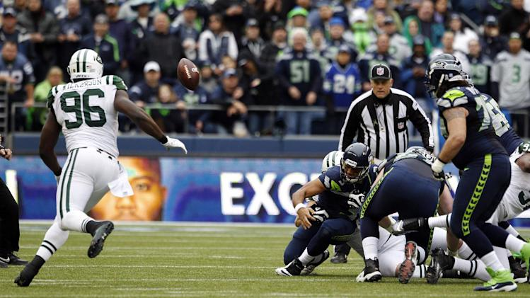 New York Jets' Muhammad Wilkerson (96) recovers a fumble by Seattle Seahawks quarterback Russell Wilson, center, in the first half of an NFL football game, Sunday, Nov. 11, 2012, in Seattle. Wilkerson ran for a touchdown on the play. (AP Photo/Elaine Thompson)