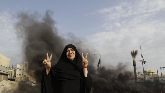 A Bahraini anti-government protester poses for a photograph flashing the victory sign in front of burning tires on a road in the village of Dumistan, Bahrain, Monday, Jan. 7, 2013. Bahrain's highest court has upheld jail sentences against 20 opposition figures convicted of plotting to overthrow the Western-allied government, including eight prominent activists facing life in prison and is almost certain to bring strong criticism from rights groups and touch off more street protests in the violence-wracked Gulf kingdom. (AP Photo/Hasan Jamali)