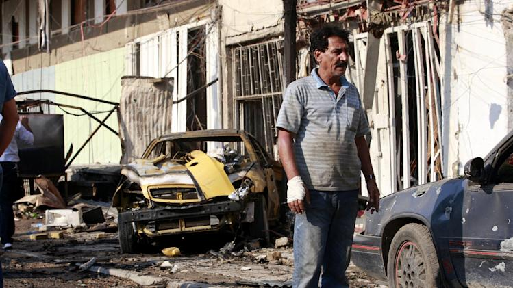 An Iraqi man stands at the scene of a car bomb attack in central Baghdad, Iraq, Wednesday, Nov. 14, 2012. Iraqi insurgents unleashed a new wave of bombings across the country early Wednesday targeting security forces and civilians, killing and wounding scores of people, police said. (AP Photo/Hadi Mizban)