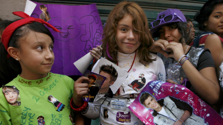Fans  hold pictures of pop star Justin Bieber near  Mexico City's main historic plaza, the Zocalo, Sunday, June 10, 2012.  The Beliebers have arrived in the chaotic streets of Mexico City, adolescents in purple and white and braving two nights on roach-infested sidewalks for a chance to be closest to the stage when teenage superstar Justin Bieber puts on a free concert Monday evening on the capital's vast central plaza.(AP Photo/Marco Ugarte)