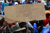 Demonstrators hold a placard during march by protesting miners in Rustenburg after a security crackdown in the restive platinum belt where officers shot dead 34 strikers exactly a month ago. South Africa's President Jacob Zuma denied Sunday his government had embraced apartheid measures in a crackdown on protesting mineworkers