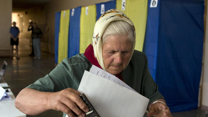 An elderly woman casts her vote in the presidential election in the eastern town of Krasnoarmeisk, Ukraine, Sunday, May 25, 2014. Ukraine's critical presidential election got underway Sunday under the wary scrutiny of a world eager for stability in a country rocked by a deadly uprising in the east. While there were no immediate reports of violence, pro-Russia insurgents were trying to block voting by snatching ballot boxes and patrolling polling stations.(AP Photo/Vadim Ghirda)