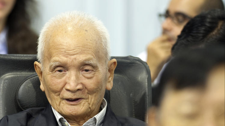 In this photo released by the Extraordinary Chambers in the Courts of Cambodia, Nuon Chea, left, who was the Khmer Rouge's chief ideologist and No. 2 leader, waits before his final statements at the U.N.-backed war crimes tribunal in Phnom Penh, Cambodia, Thursday, Oct. 31, 2013. Former Khmer Rouge leader Nuon Chea has denied all charges against him on the last day of a trial for leaders of the Cambodian regime widely blamed for the deaths of some 1.7 million people. (AP Photo/Extraordinary Chambers in the Courts of Cambodia, Mark Peters)