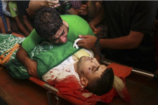 A Palestinian mourns over the body of a gunman during his funeral in Gaza