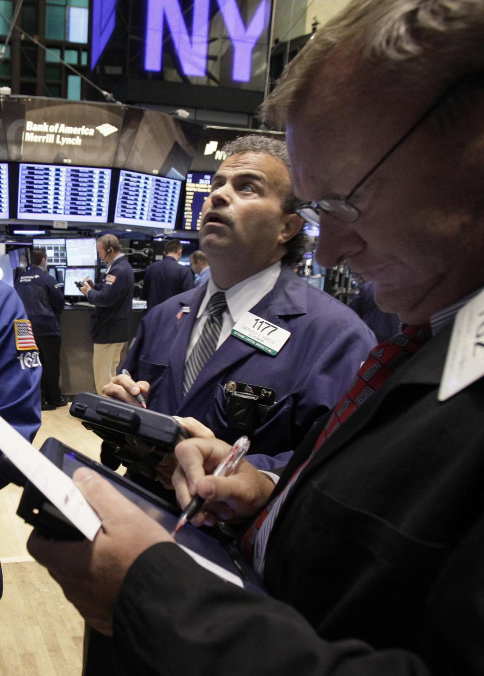 Gerard Farco, left, works with fellow traders on the floor of the New York Stock Exchange Monday, Sept. 19, 2011. (AP Photo/Richard Drew)