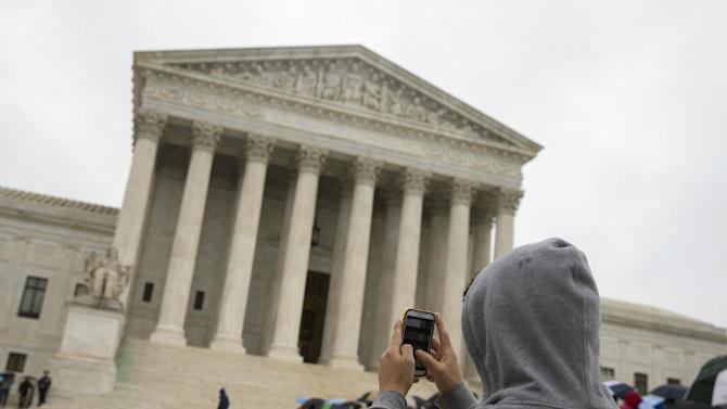 a Supreme Court visitor using his cellphone to take a photo of the court in Washington.