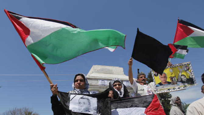 A Palestinian woman holds a portrait of Maysara Abu Hamdiyeh during a rally in Gaza City, Tuesday, April 2, 2013. Abu Hamdiyeh, 64, who was serving a life sentence for his role in a foiled attempt to bomb a busy cafe in Jerusalem in 2002, died Tuesday of cancer in an Israeli jail. Tensions are high in Israeli lockups where thousands of Palestinian security prisoners are being held. (AP Photo/Hatem Moussa)
