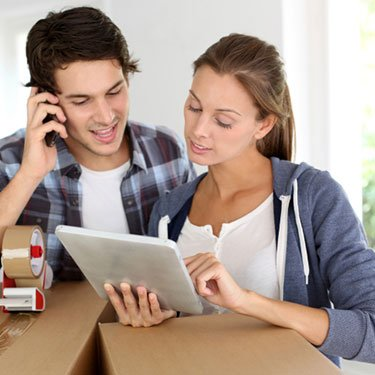 Couple-on-phone-with-boxes-looking-at-ipad_web