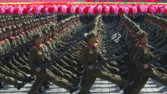 FILE - In this April 15, 2012 file photo, North Korean soldiers march in front of flower waving civilians during a mass military parade in Pyongyang's Kim Il Sung Square to celebrate 100 years since the birth of the late North Korean founder Kim Il Sung.  North Korea has replaced its defense minister with a hardline military commander believed responsible for deadly attacks on South Korea in 2010, diplomats in Pyongyang said Thursday, Nov. 29, 2012. It is the latest in a series of high-profile appointments leader Kim Jong Un has made since he took power nearly a year ago.  (AP Photo/David Guttenfelder, File)
