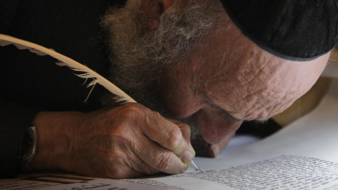 FILE - In this Sunday, March 14, 2010 file photo, an ultra-Orthodox Jewish man writes some of the last words in a Torah scroll before it is taken from the Western Wall into the Hurva synagogue in Jerusalem's Old City. Software developed by an Israeli team of scholars led by Moshe Koppel, of Bar Ilan University near Tel Aviv, is giving intriguing new hints about what researchers believe to be the multiple hands that wrote the Bible. (AP Photo/Dan Balilty, File)
