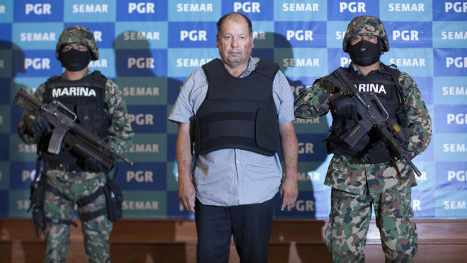 "Mexican Navy officers flank Mario Cardenas Guillen, also known as ""El Gordo"" and ""M-1,"" during his presentation to the media in Mexico City, Tuesday, Sept. 4, 2012. Authorities says Cardenas Guillen, a top leader of the Gulf drug cartel, is the brother of Osiel Cardenas Guillen, who led the cartel until he was detained in 2003. Osiel Cardenas was extradited in 2007 to the United States and sentenced to 25 years in prison. (AP Photo/Alexandre Meneghini)"