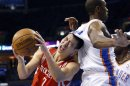 Houston Rockets guard Jeremy Lin, left, grimaces as he is fouled by Oklahoma City Thunder forward Serge Ibaka, right, in the first quarter of Game 1 of their first-round NBA basketball playoff series in Oklahoma City, Sunday, April 21, 2013. (AP Photo/Sue Ogrocki)