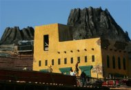 Construction workers walk past a mock volcano in the Fishermen's Wharf, one of Macau's largest entertainment parks and casinos, under construction at the Outer Harbour area in Macau in this August 3, 2005 file photo. REUTERS/Paul Yeung/Files