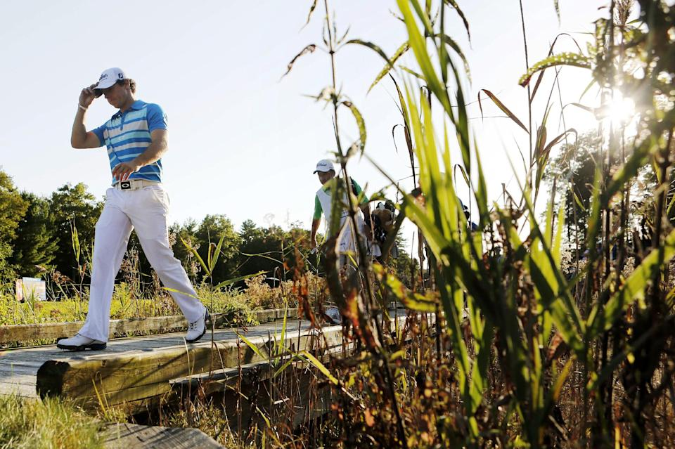 Rory McIlroy, left,   of Northern Ireland, walks onto the 18th green during the final round of the Deutsche Bank Championship PGA golf tournament at TPC Boston in Norton, Mass., Monday, Sept. 3, 2012. McIlroy won the tournament. (AP Photo/Michael Dwyer)