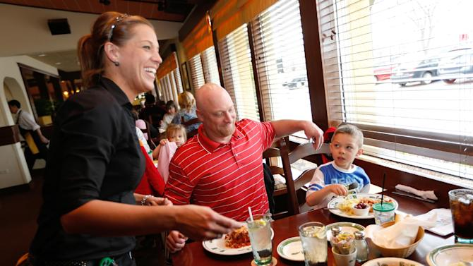 IMAGE DISTRIBUTED FOR OLIVE GARDEN - Logan Ray and his father share lunch at Olive Garden in Naperville, Ill., on Take Our Daughters and Sons to Work Day. To celebrate the day, families can receive a free kid's meal with every adult entrée purchased on Thursday, April 25, 2013. (Scott Boehm/AP Images for Olive Garden)