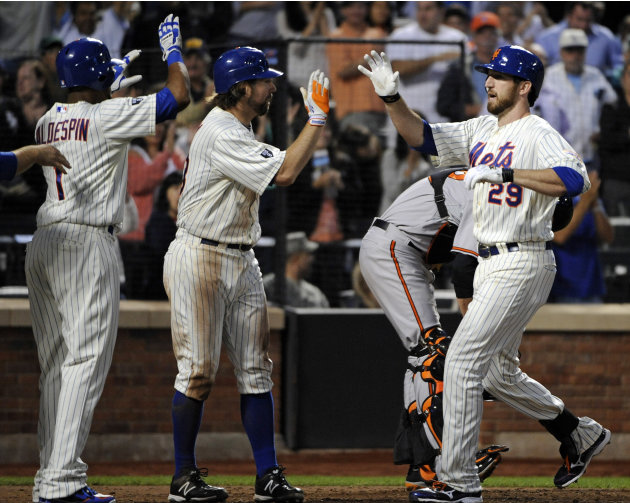 New York Mets' Ike Davis (29) is greeted by R.A. Dickey and Jordany Valdespin, left, after Davis hit a grand slam during the sixth inning of an interleague baseball game against the Baltimore Orioles,