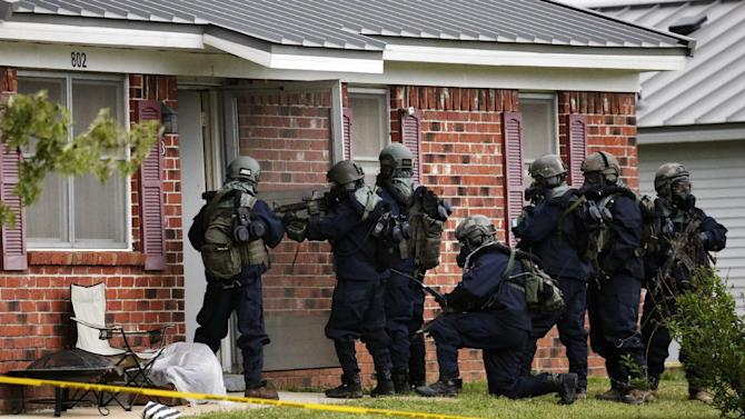 Armed federal agents wearing hazardous material suits and breathing apparatus entered the West Hills Subdivision home of Paul Kevin Curtis in Corinth, Miss., Thursday evening April 18, 2013. Law enforcement officials blocked off the dwelling after taking Curtis into custody under the suspicion of sending letters covered in ricin to the U.S. President Barack Obama and U.S. Sen. Roger Wicker, R-Miss. (AP Photo/Rogelio V. Solis)
