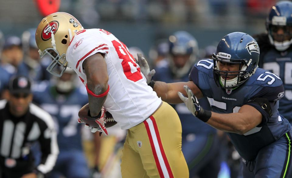 San Francisco 49ers'  Vernon Davis, left, is pushed out of bound by Seattle Seahawks'  K.J. Wright in the frist half of an NFL football game in Seattle Saturday, Dec. 24, 2011. (AP Photo/John Froschauer)