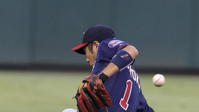 Minnesota Twins shortstop Tsuyoshi Nishioka attempts to field a single by Texas Rangers' Elvis Andrus in the third inning of a baseball game, Monday, July 25, 2011, in Arlington, Texas. (AP Photo/Tony Gutierrez)