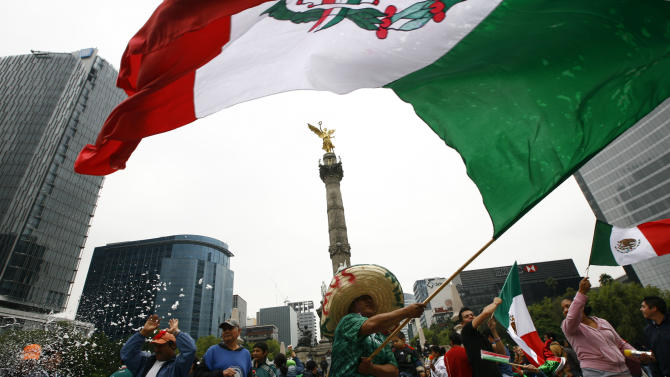 Fans of Mexico's soccer team celebrate their team's 2-1 victory over Brazil and clenching the gold medal at the London 2012 Summer Olympics, below the Angel of Independence monument in Mexico City, Saturday, Aug. 11, 2012. (AP Photo/Marco Ugarte)