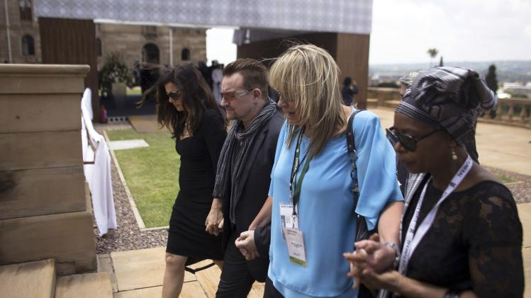 Musician Bono and his wife Hewson walk with La Grange, former assistant of former South African President Nelson Mandela, after viewing Mandela's coffin in Pretoria
