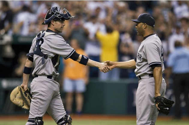 Yankees catcher Stewart congratulates closer Rivera after beating the Rays during an 11-inning MLB game in St. Petersburg