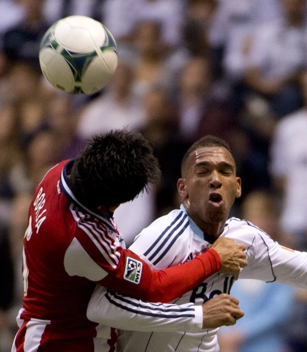 Vancouver Whitecaps FC's Matt Watson, right, fights for control of the ball with Chivas USA's Carlos Borja during the first half of an MLS soccer game in Vancouver, British Columbia, Wednesday, June,