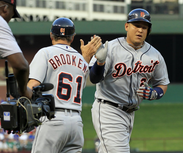 Detroit Tigers' Miguel Cabrera (24) slaps the hand of third base coach Tom Brookens (61) on the way to the plate, after hitting a three-run homer during the third inning of a baseball game against the