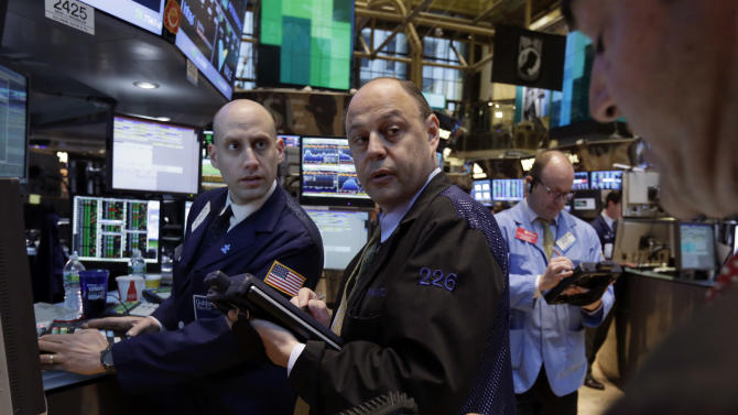 Specialist Meric Greenbaum, left, works with traders on the floor of the New York Stock Exchange Monday, April 29, 2013. World stock markets were mostly higher Tuesday April 30, 2013, brushing off tepid Japanese manufacturing data a day after the Standard & Poor's 500 index closed at another all-time high. (AP Photo/Richard Drew)