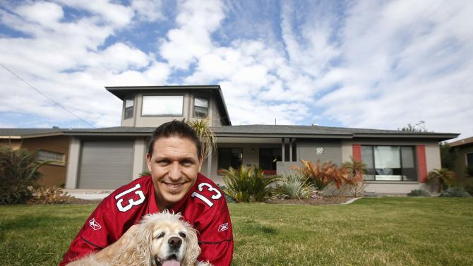 In this Tuesday, Jan. 27, 2015 photo, Dominic Hrabe holds the family dog, Gracie, in front of his home that he is renting out for Super Bowl weekend in Phoenix. The family is vacating the house for two nights after using airbnb to rent their place to people attending the NFL Super Bowl football game. (AP Photo/Ross D. Franklin)